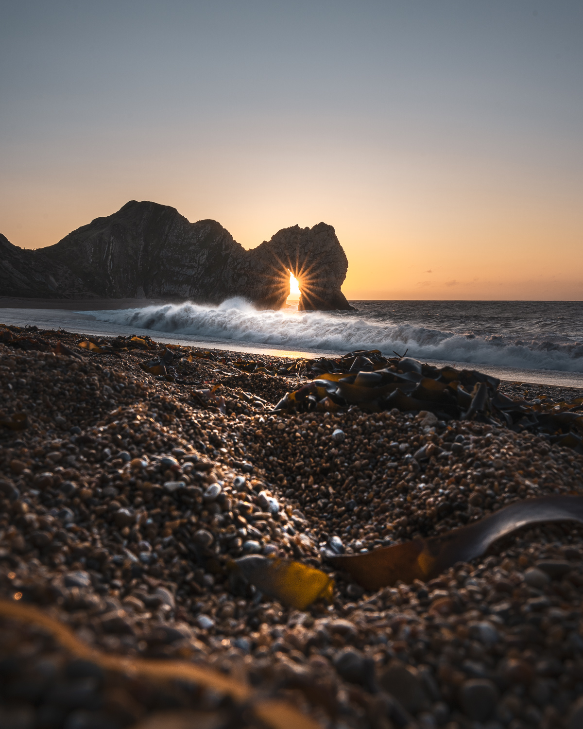 durdle door sunrise through arch