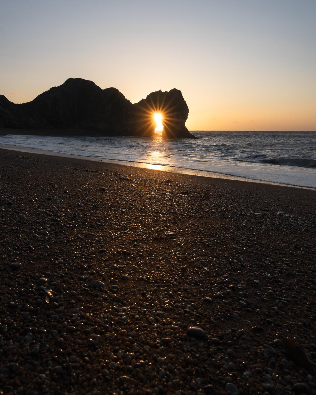 durdle door sunrise through arch